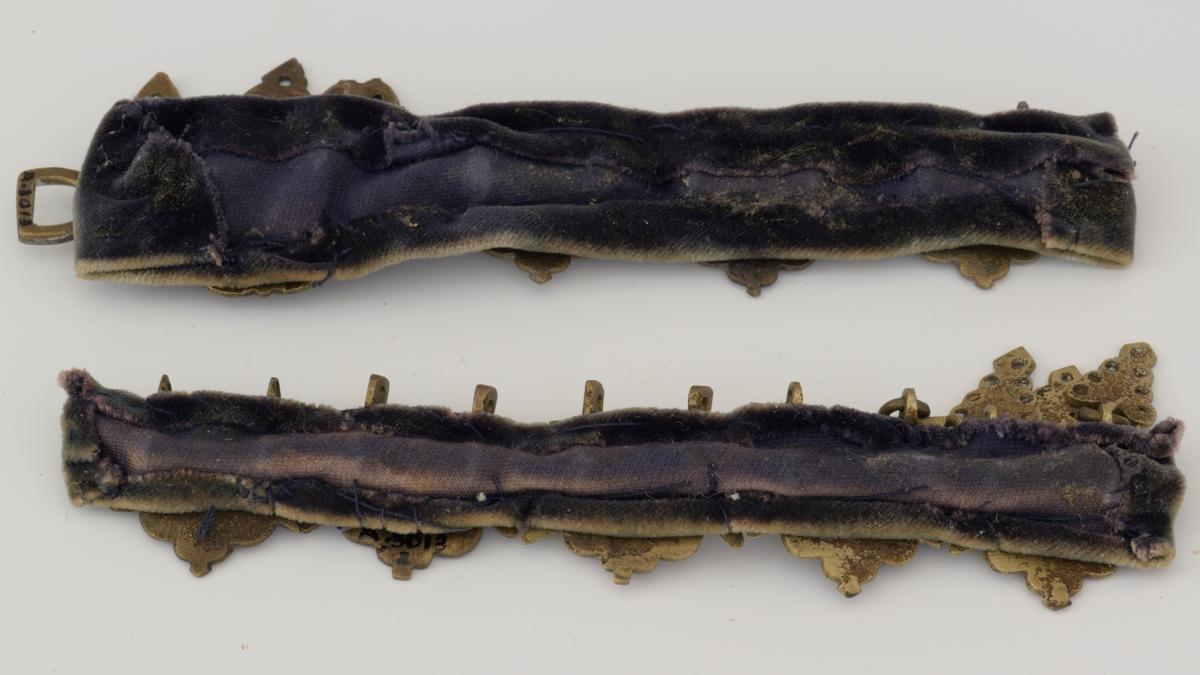 A: Fløyelsbånd med 5 messingledd, 3 faste ringer på 2 av leddene hengende blader. B: Bånd og 3 ledd som A, 4 ledd, de forreste, større med avvikende dekor og blader Det finnes også 13 like ledd til, + 2 avvikende, og 7 blad.