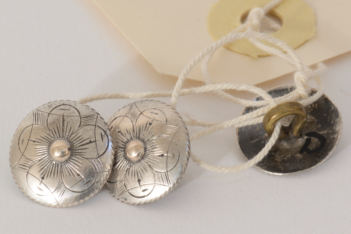 3 støpte sølvknapper med hempe på baksiden. Blomsterdekor.