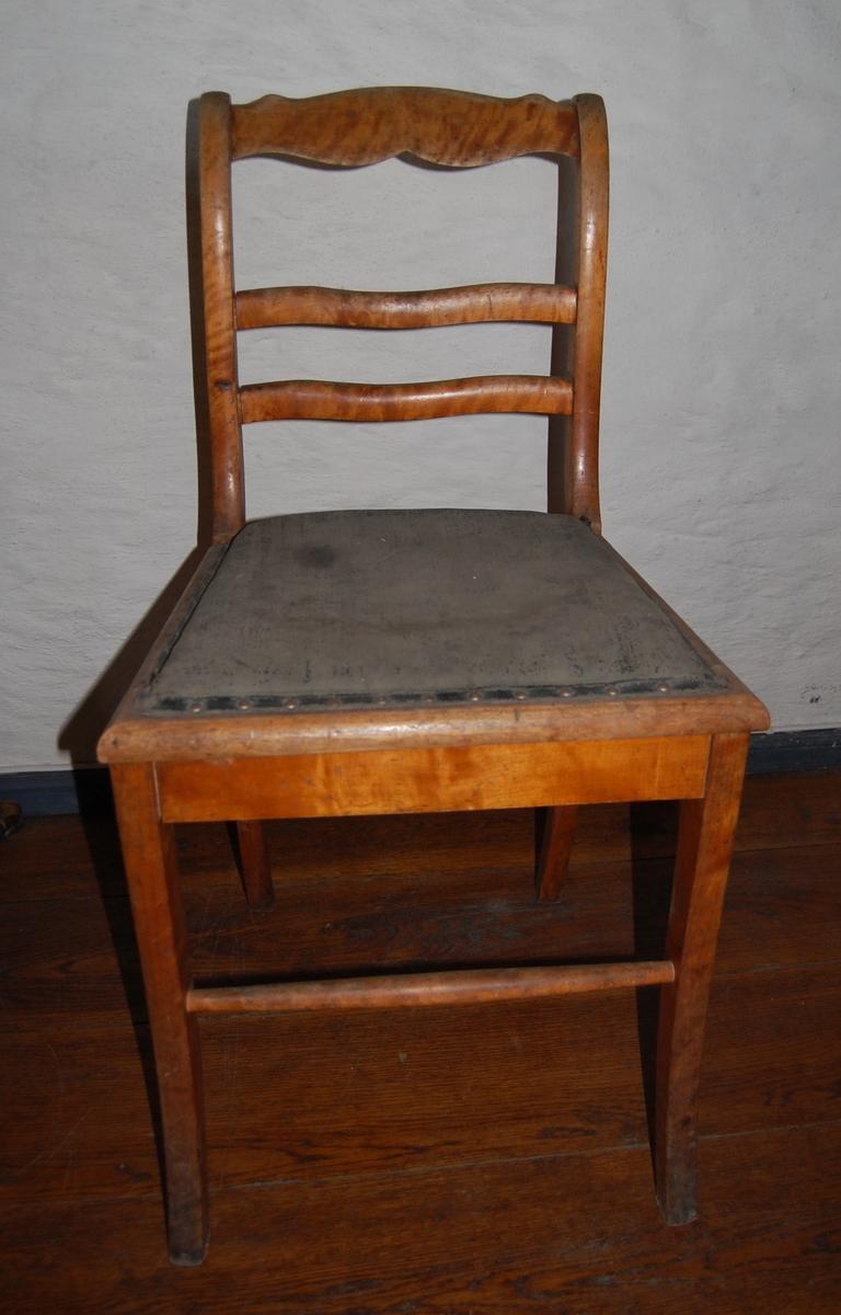 Trestol med sete trukket i kunstskinn (?). Tre ryggsprosser, den øverste profilert. Likner AS.313-317, Biedermeier-stil. Slitt setetrekk.