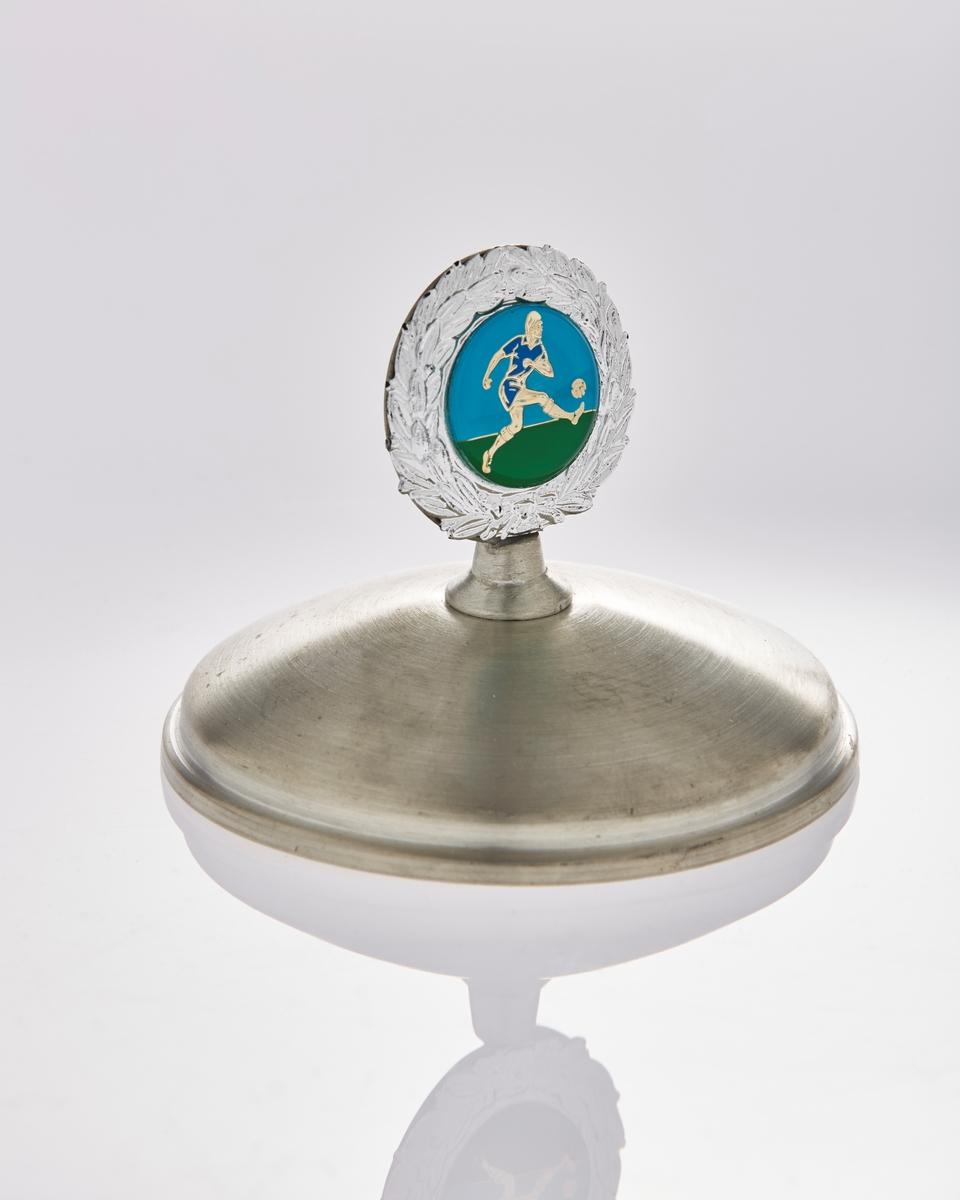 Emblem: krans med bilde av en fotballspiller. Emaljert i blått og grønt.