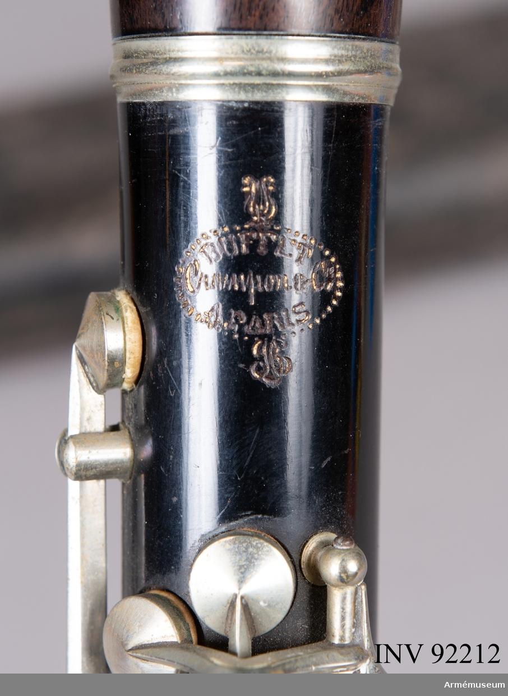 Ess-klarinett med tillhörande fodral.  Ess-klarinetten är stämd en kvart över B-klarinetten. Den är av mindre format och har utformats för att ge en mer gäll ton. Därför används de i större orkestrar för sin speciella effekt, liksom i militärorkestrar.