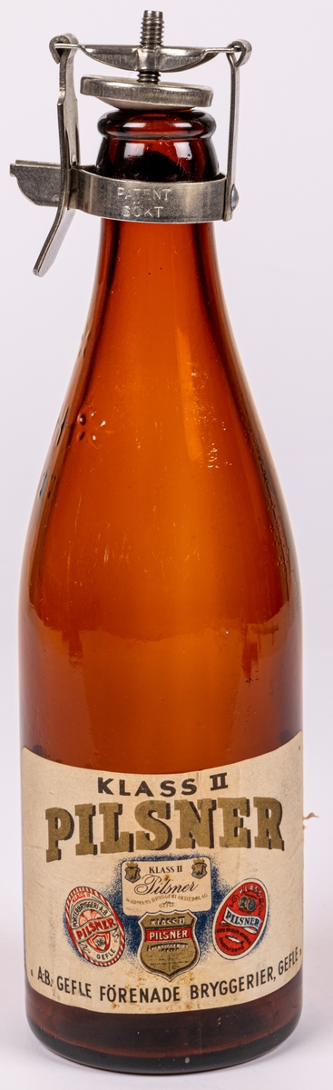 """Flaska. Brunt glas. Patentkork, metall. Etikett: """"PILSNER KLASS II GEFLE"""" m.m. A.B. Gefle förenade bryggerier, Gefle."""