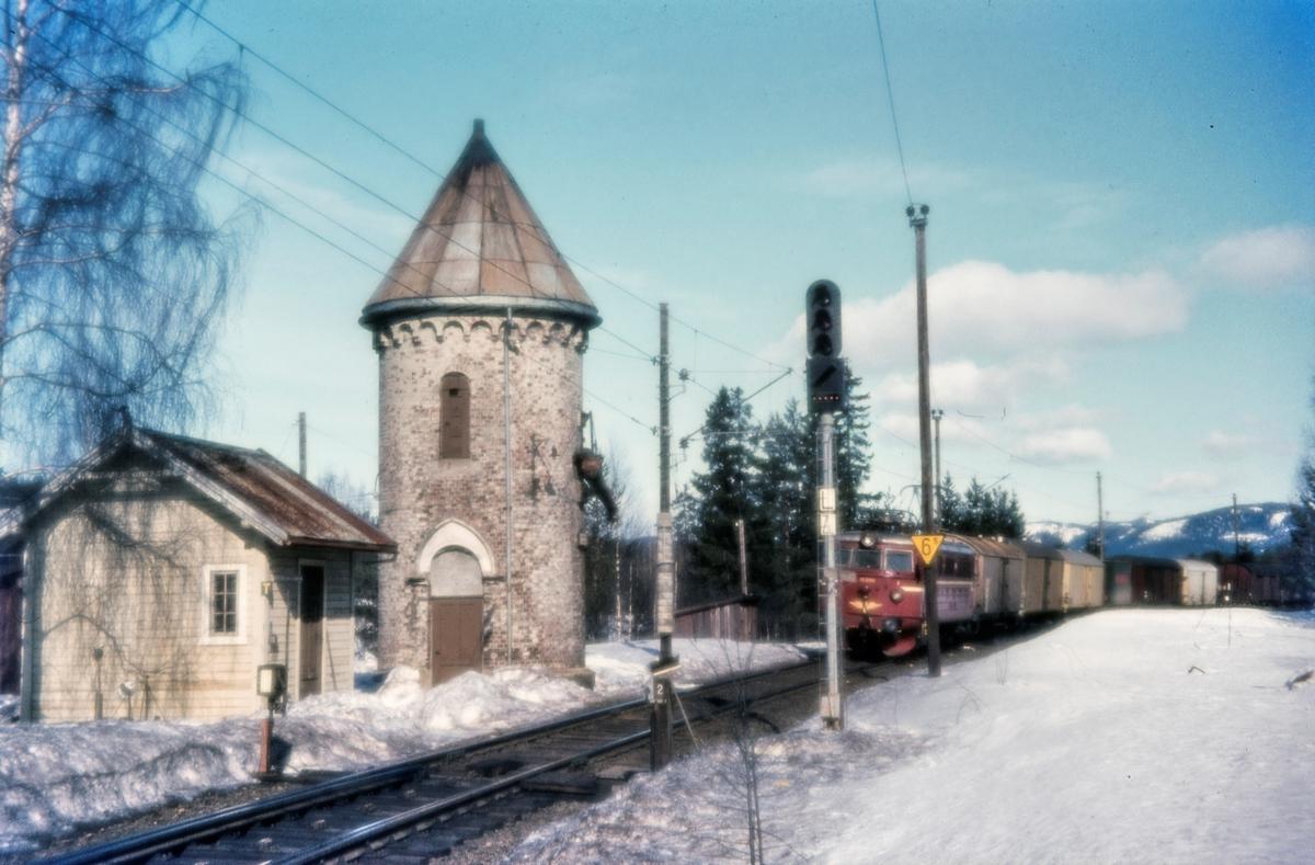 Vanntårneet på Stryken stasjon på Gjøvikbanen. I bakgrunnen elektrisk lokomotiv El 13 med godstog
