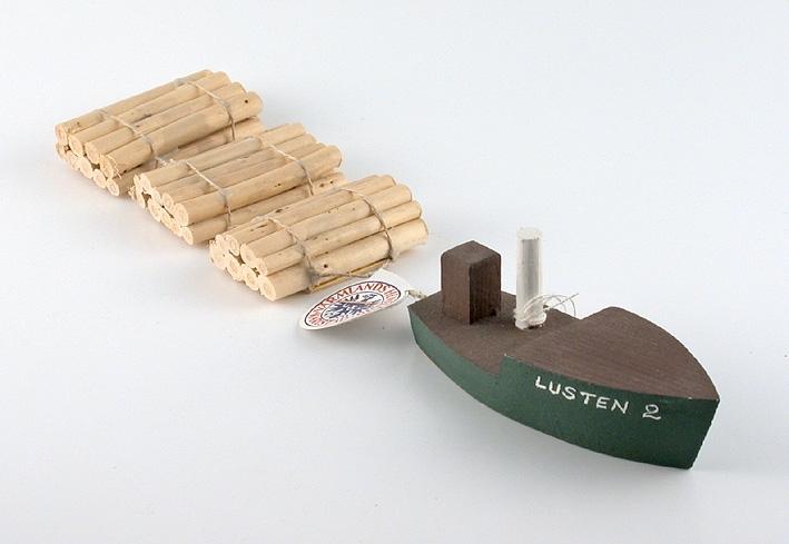 """En träbåt i miniatyr, med timmersläp efter, med texten """"Lusten 2""""."""