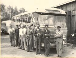 Personale ved NSB Hølandsrutene foran turistbuss utenfor ver