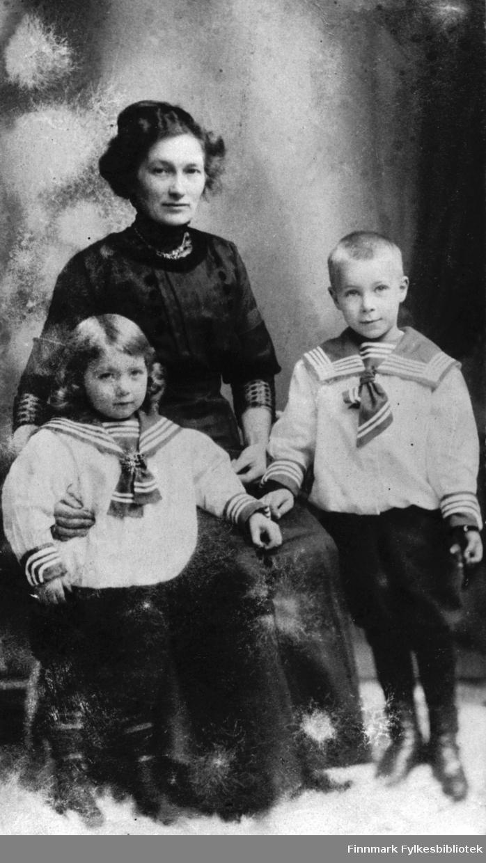 Portrett fra familien Noodt. Mor, Hanna Noodt, fotografert med sønnene Håkon og Leif. Guttene er kledd i hvite matrosedrakter med svarte bukser.