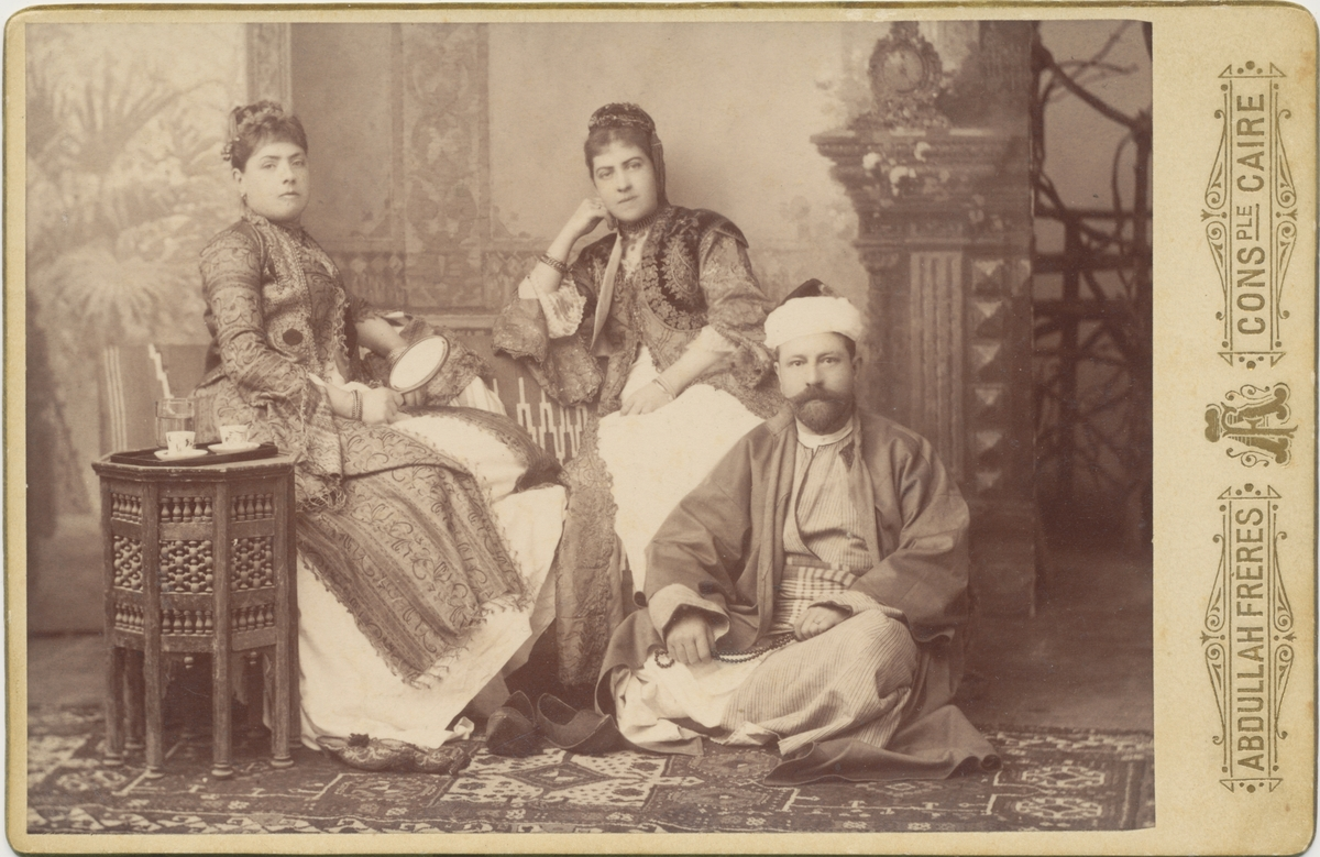 John och Antonie Rettig, sittande i en fotostudio iklädda orientaliska kläder. I mitten sitter Antonies syster Sophie-Louise von Plessen.
