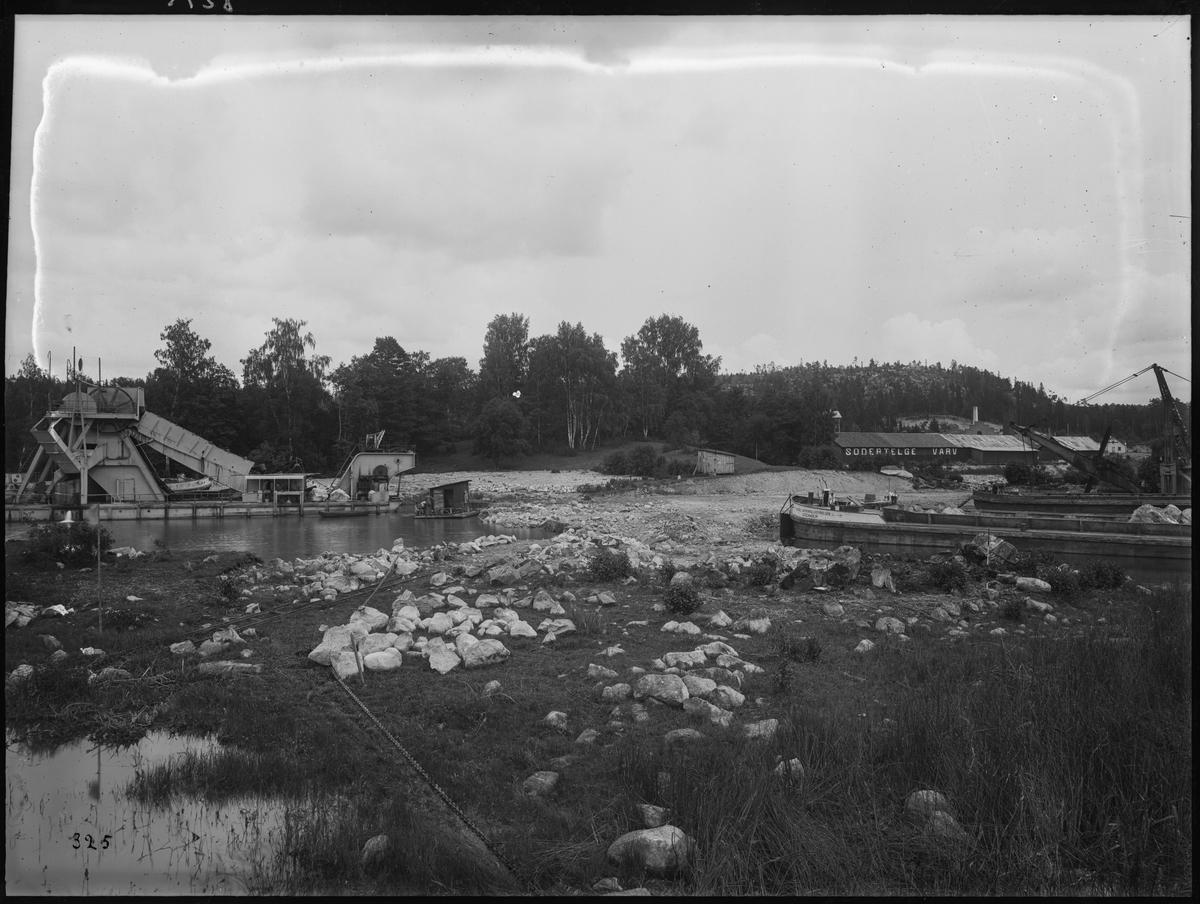Bygget av Södertälje kanalverk. Ett mudderverk samt två pråmar vid Södertelge varv.
