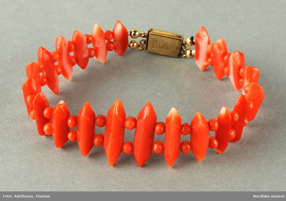 Armband med stående lavettformade  rödrosa koraller, mellan varje lavettform är placerade två små korallkulor. Lås i 18 karat guld enligt stämpel tillverkat 1948.    /Cecilia Wallquist 2019-02-19