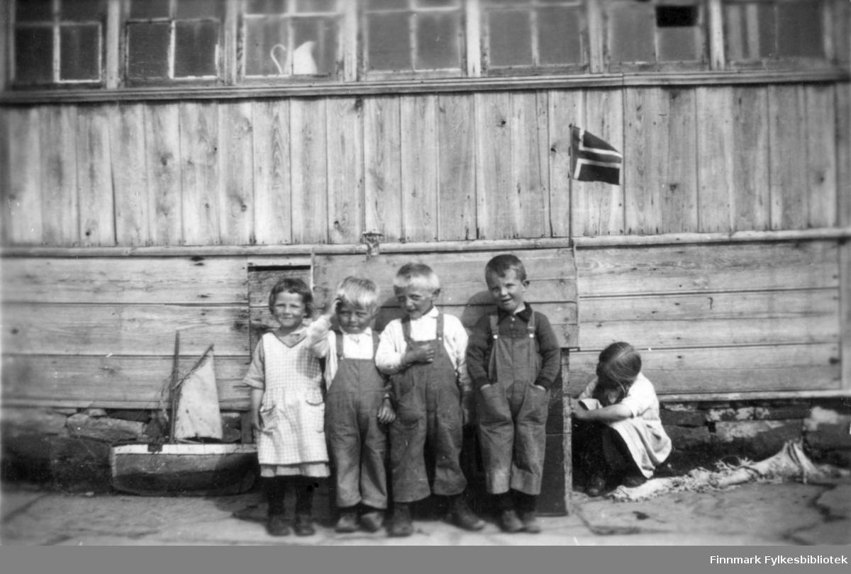 Tre gutter og to jenter fotografert foran et hus (havnefogd Nilsen sitt hus) i Salttjern. Kanskje det er 17.mai siden Norsk flagg er med? En seilbåt leketøy ligger på bakken ved siden barn.