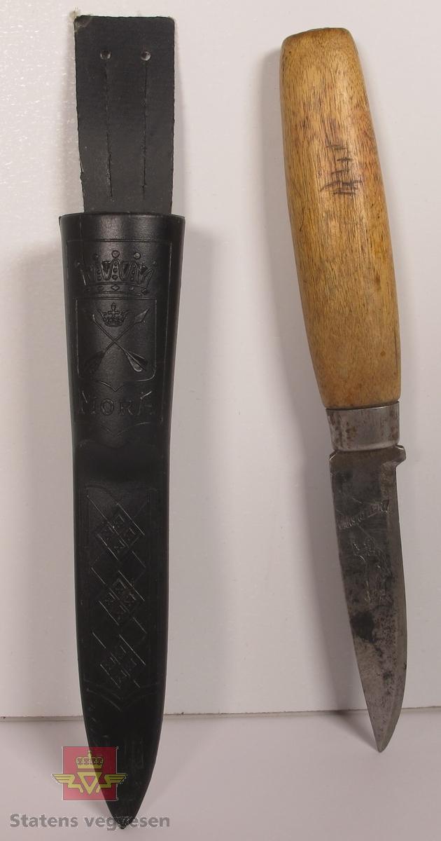 Luntekniv med knivslire i svart plast som har hempe for festing på belte. Skaft av lakkert treverk, og knivblad som ser ut til å være håndsmidd. Knivbladet har innskriften GRUBERNES SPRÆNGSTOFFABRIKER A-S på den ene siden. Den andre siden har innskriften VARSKO HER! med omrisset av en mann under.
