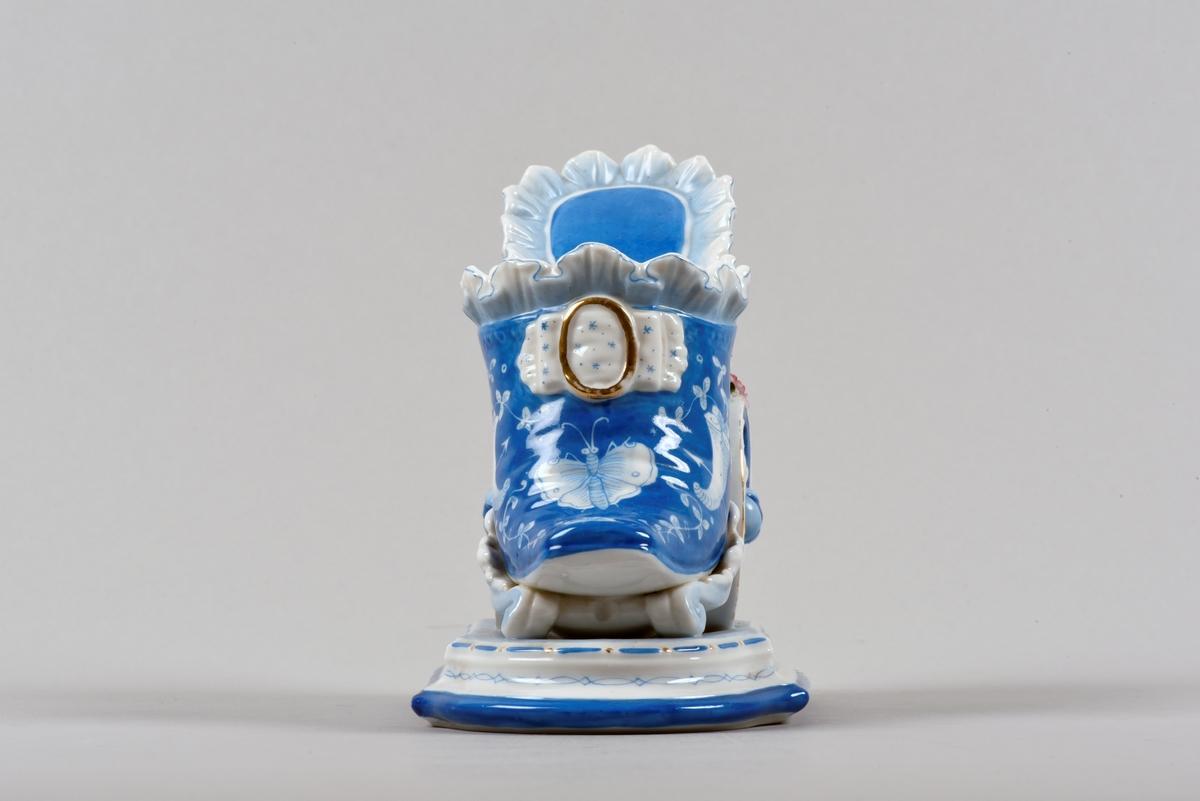 Prydnadsföremål, vas, tillverkat av bemålat vitt porslin. Vasen är i form av en sko på hjul, som dras av en putti. Selen består av en blomstergirland.
