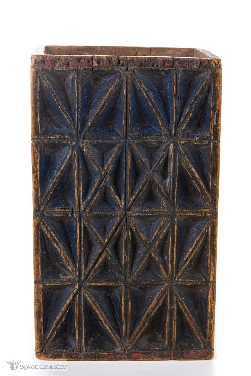 Et geometrisk mønster sammenkomponert av kryss skåret ut i dyp karveskurd på alle eskens sider. Nederst på esken er det skåret ut en tannbord.