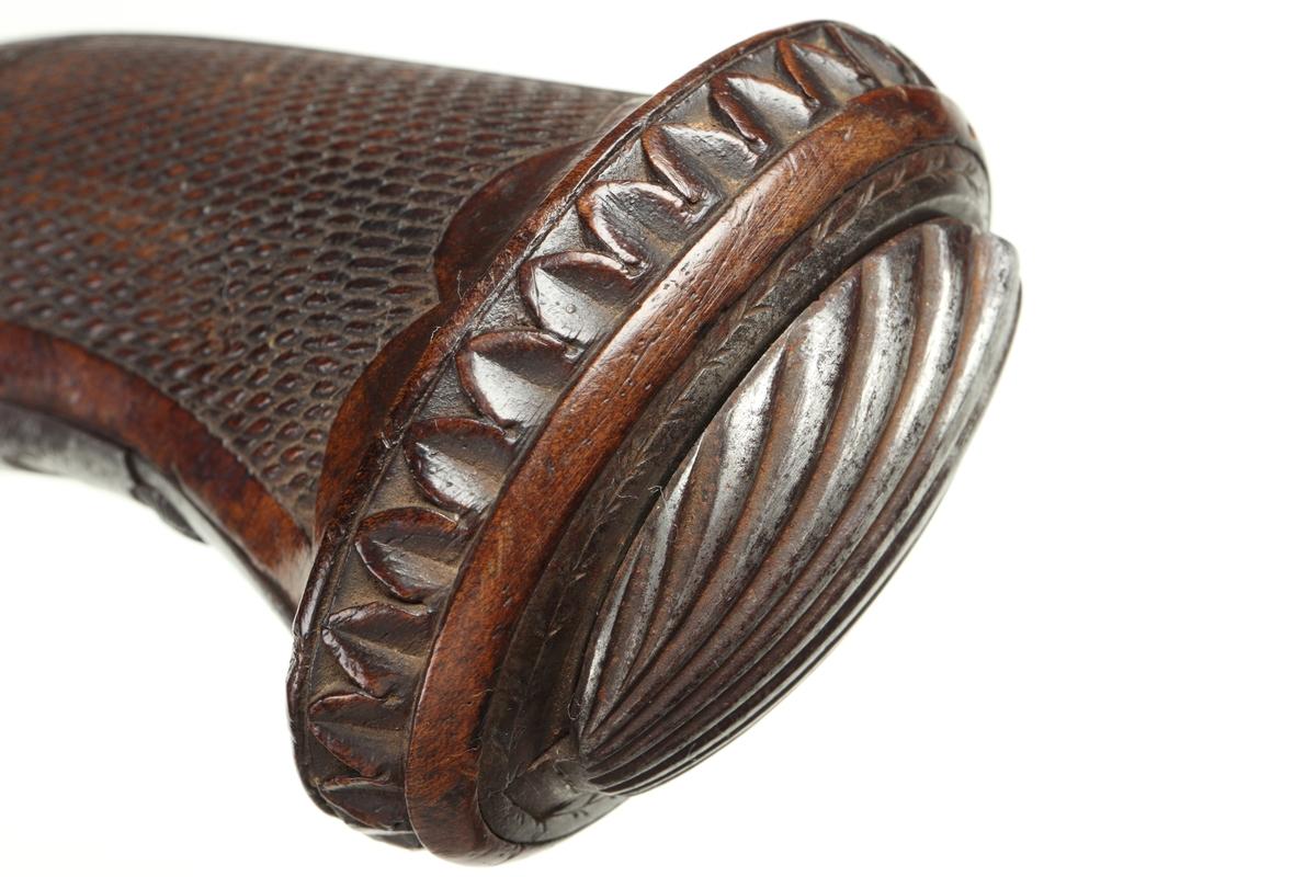 Målskjutningspistol i slaglåsutförande med halvstock av päronträ. Kolven är nätskuren och försedd med en snäckformad kolvknapp som sitter fast med ett charner, d.v.s. ett gångjärnförsett lock i form av en snäcka. Utrymmet under kolvknappen har använts till att t.ex. förvara tändhattar i. Pistolens alla metalldelar är tillverkade av polerat stål och ör cicelerade. Varbygeln har ett extra utvändigt fingergrepp. Pipan har en åttakantig genomskärning, samt har ett fastlött mässingssikte längst fram. Pipan är räfflad invändigt med en innerdiameter på 16mm. Inskrivet i huvudkatalog 1974.