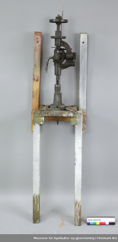 """Boremaskinen står på et hjemmesnekret stativ som er ment til å festes til veggen. Stativet har to skråstilte bein, en """"hylle"""" bestående av to langsgående  og to tverrgående kiler som boremaskinen er festet til og to lektere bak til å feste ved en vegg."""