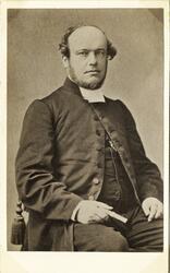 Foto av en man i prästrock med väst och prästkrage. Längs vä