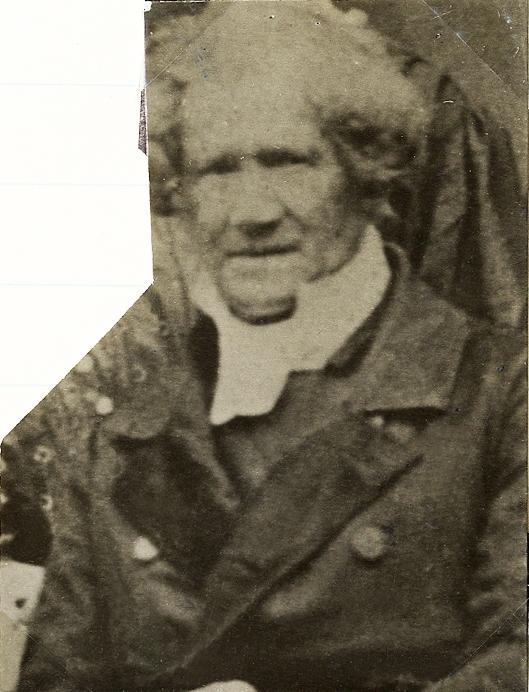 Foto av en äldre man med polisonger, klädd i rock, prästkrage m.m.  Bröstbild, halvprofil, Ateljéfoto.
