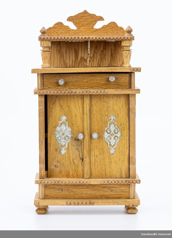 Skänkskåp, dockskåpsmöbel, i nyrenässansstil med två lådor och en dörr. Se även SuM 0625-0629:1-4.