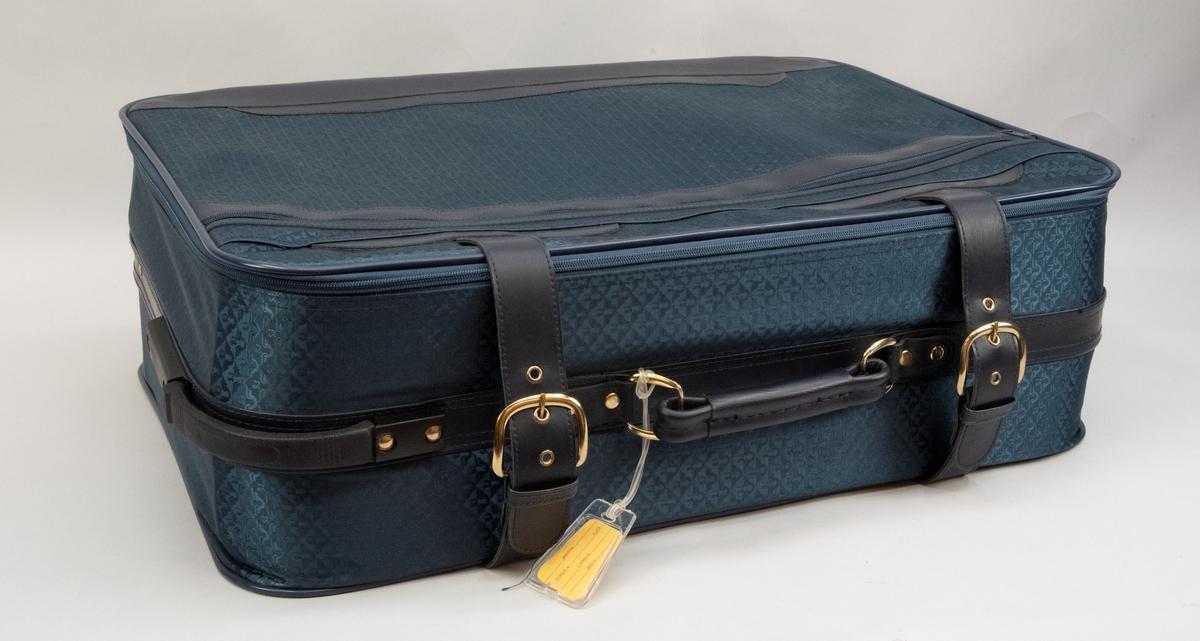 Blå resväska med vävt tyg med SJ:s logga, två spännremmar av konstläder och ett handtag klätt med konstläder. Två hjul i hörnet mellan ena kortsidan och långsidan och ett handtag i motstående hörn. Lock med dragkedja. Ytterfack med dragkedja på utsidan av locket och en ficka på insidan. Resårband inuti.