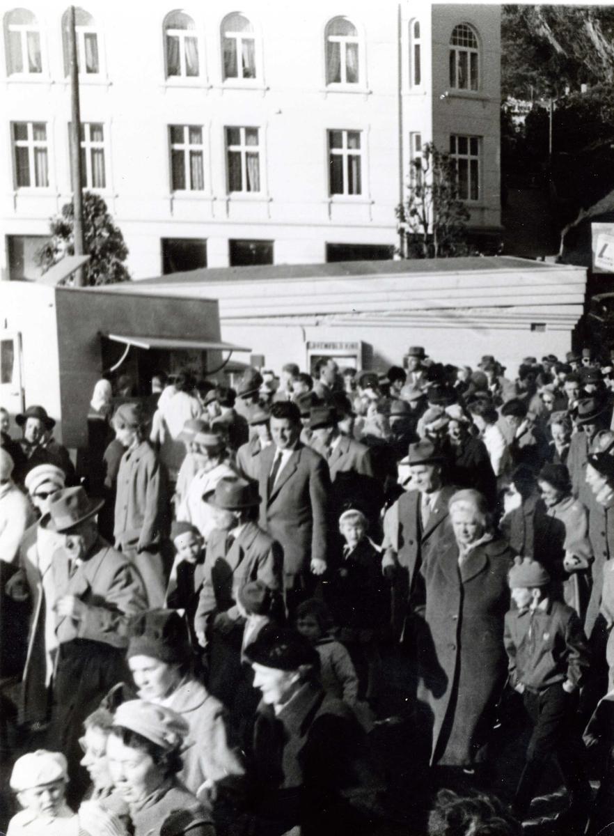 Mange mennesker passerer Lorchenestorget på vei over Hellebroa, ca år 1960. Vi skimter del av Kjøttkontrollen. Rasmus Rønnebergsgt 1 i bakgrunnen. Fish and Chipsvogna til venstre.