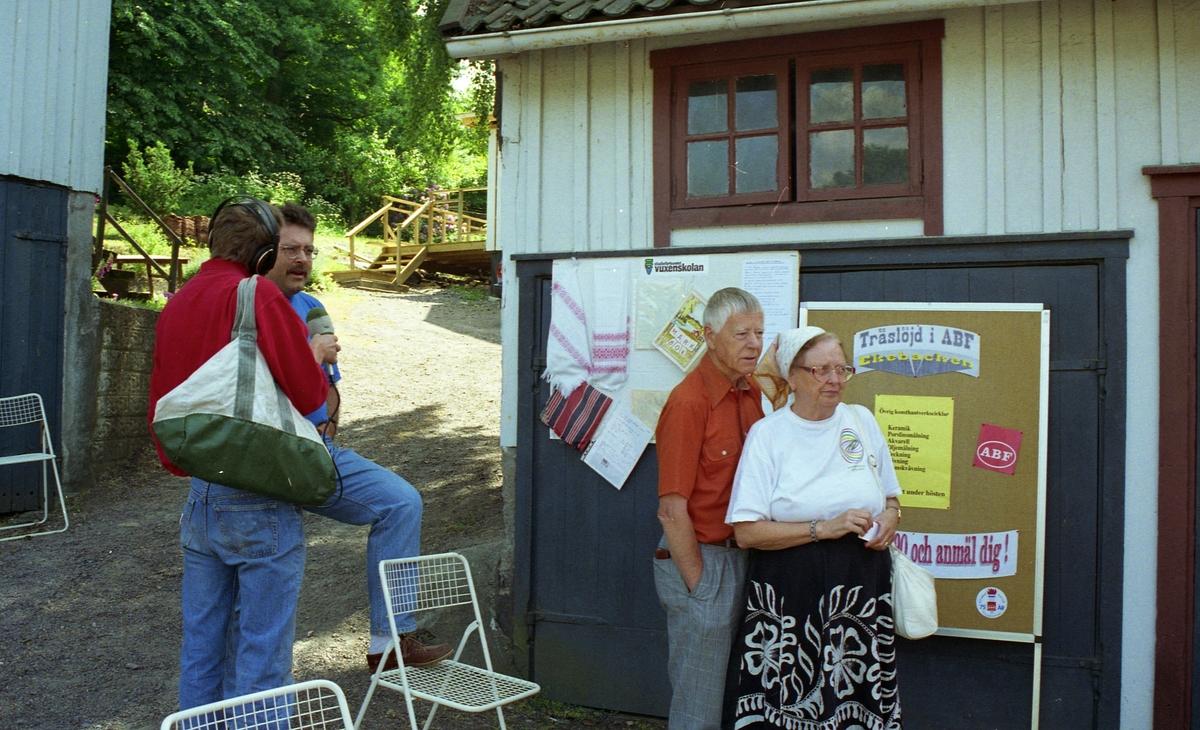 Invigning av Ekebackens Hantverksgård (tidigare John Lindströms möbelsnickeri) på Gamla Riksvägen 79, början av 1990-talet. Från vänster: (vänd från kameran) Lars Andersson från Närradion som intervjuar Staffan Bjerrhede. Till höger: Göthe och Ulla Andersson (Sporred).