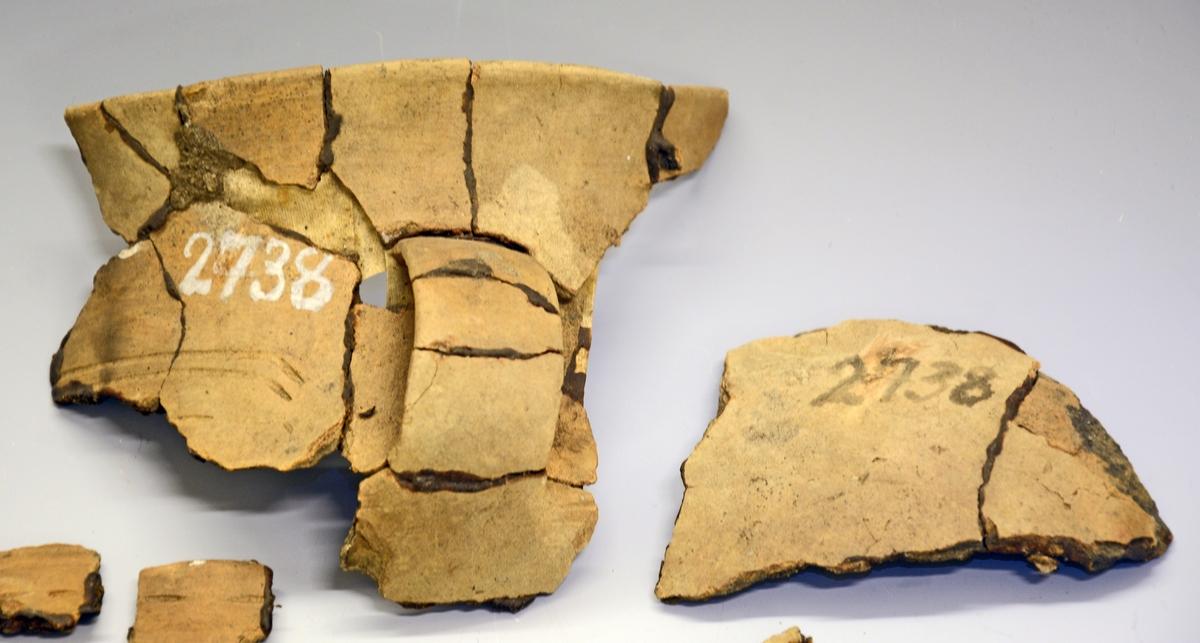 Fra protokollen (J. S. Munch, 1952):  Leirkar i fragmenter, av hovedtypen Rygh 361, vanskelig å bestemme nærmere. Karet har ikke helt flat bunn, men ståflaten markert med punktsirkel. Buken er svært lav og vid, bukovergangen skarp, og skulder og hals jevnt svinget. Hanken er langstrakt og lav, uten ornering. Karets ornering innskrenker seg til skulderen og består av enkle streker, avsluttet ved hanken. Godset er tynt, grålig, med jevnt glattete flater. Størrelse ubestembar. Mesteparten av bitene til karet synes å foreligge.  Disse saker (TGM-SM.2738-41) er funnet samlet i en gravhaug av langstrakt form, 20 fot lang, omgitt av en grøft. I haugen var 3 brannsteder, mellom dem lå sakene. Noen forrustete jernfragmenter ligger også ved funnet. Datering: Yngre romertid eller overgangen til folkevandringstid.