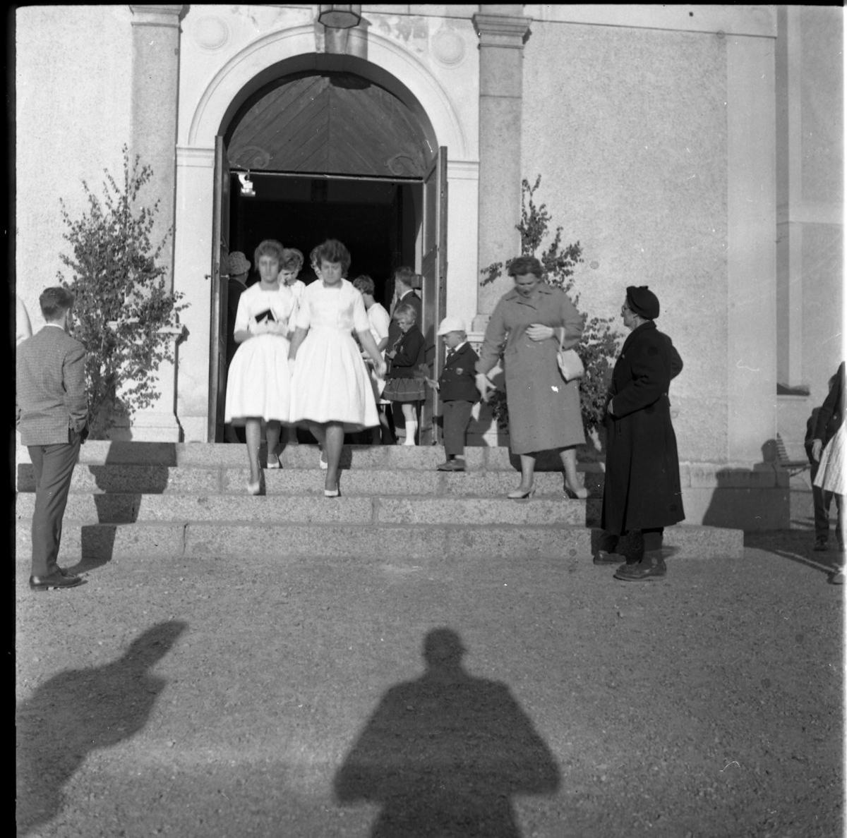 Kvinnliga konfirmander på väg ut ur Gränna kyrka. Vid trappan står barn och vuxna. I förgrunden fotografens skugga.