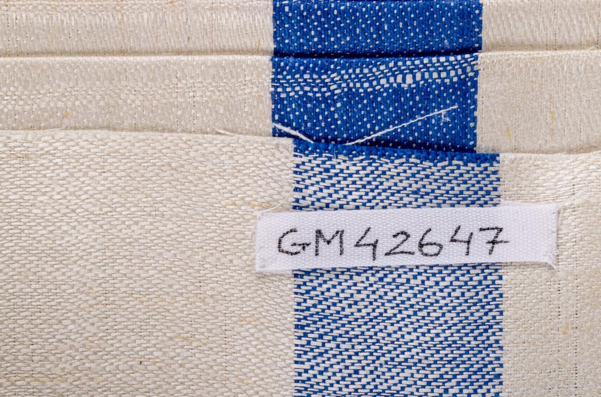 Oklippt, maskinvävd handduksväv av hellinne tillverkad vid Torsåkers linnefabriks aktiebolag. Vävd i tuskaft med naturfärgad botten med blåa effektränder. Försedd med pappersetiketter med tillverkarens emblem.