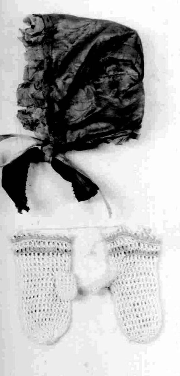 Lue med bredt pannestykke og et innfelt stykke i nakken. Lua er sydd av lilla silkestoff, kanting av lilla silke, over foldelagt tyllblonde.Pyntet med en blå silkesløyfe på hver side.Fôr av lin.
