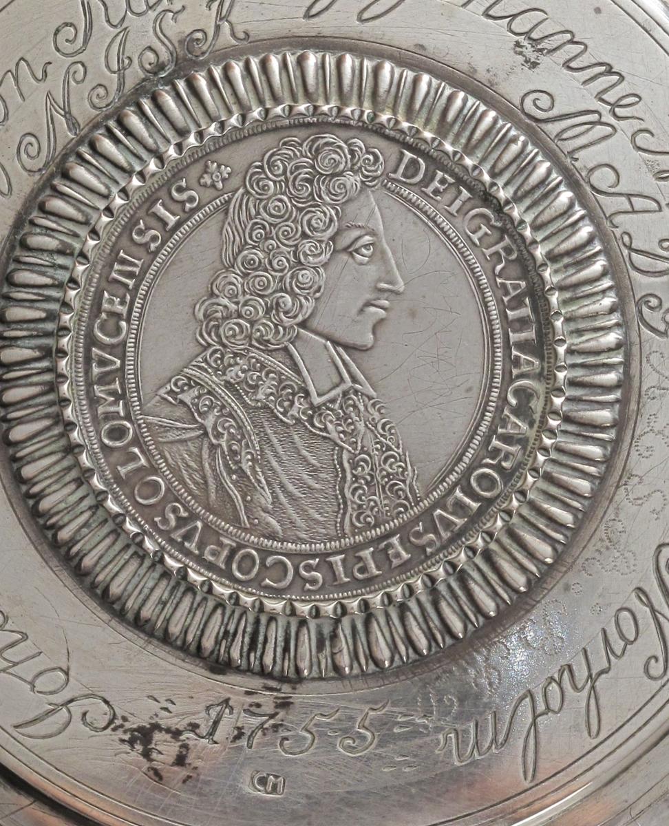"""Stentøykrus m. lokk i sølv, lokket laget 1755.   Flatt lokk m. buet, profilert kant, innsatt mynt  m. radiært riflet innr. grav. :   Johannes Salwesøn Kallevig,   Johanne NielsDatter Norholm, 1755,  samt   initialer for seinere eiere.  Sølvsmedstempel.   Mynten profilportrett m. innskr: DEI GRATIA CAROLVS   EPISCOPVS OLOMVCE N(?) SIS""""  reversen kronet våpen m.  ørner etc. :  DUX LOTHAR ET BAR S R I PCPS   RE CA BOKO 1704.   Lokkgrep som stående blad m. opprullede fliker.    Lokket montert på sylindrisk stentøykrus,  nederst brunt,  riflet feldt, derpå glatt, så lyst, riflet  feldt, buet,  profilert hank forts."""