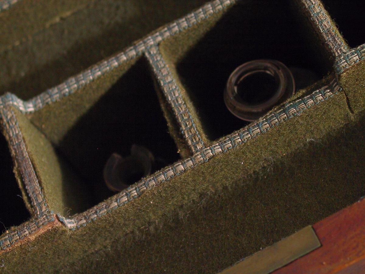 Reiseapotek av mahogny. Bæregrep av messing  på sidene. Sindrig låsmekanise. Det rombiske nøkkelhullskilt av  messing på hver av de to dører er narreskilt. For å åpne  apoteket  må man låse opp døren som holder topplaten nede. Platen er  hengslet  i bakkanten, og danner lokk over et par smårom, som er  trukne med  grønt ullstoff, kantet med agramaner. Ved et i  fjærsystem låser lokket de to dørene, og bak dem finner man:  1) flakonger for medikamenter, med glasspropper  og med etiketter, stående i hyller trukne med  grønt ullstoff og agramaner.  2) småskuffer av mahogny, med håndgrep av messing, til  medikamenter. Skuffenes front er mahogny, resten eik.  Det finnes intet trade eard eller inskripsjoner.  Medisinene var  forordnet av hennes reisemedicus dr. Johann  Gottfried Ehrichsen, og de var laget ved  hoffapoteket i London