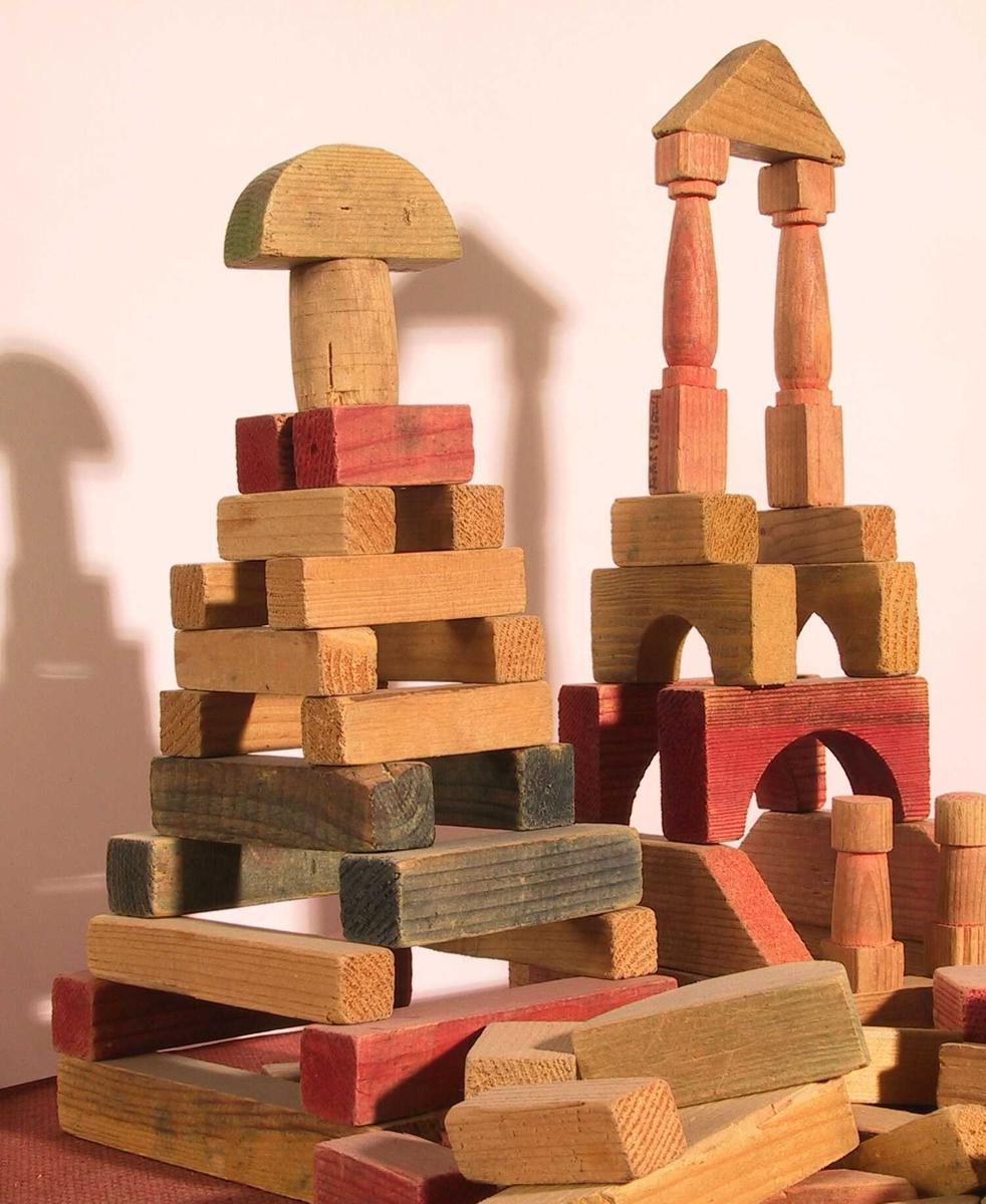Byggeklosser.   Tre   Eske med treklosser av ulik størrelse og form,   malt i rødt, gult, blått, en del umalte.  De fleste skvære i kantene, enkelte søyler, trapesformer.  Tilstand mars 1982: Tydelig brukte, men bra.