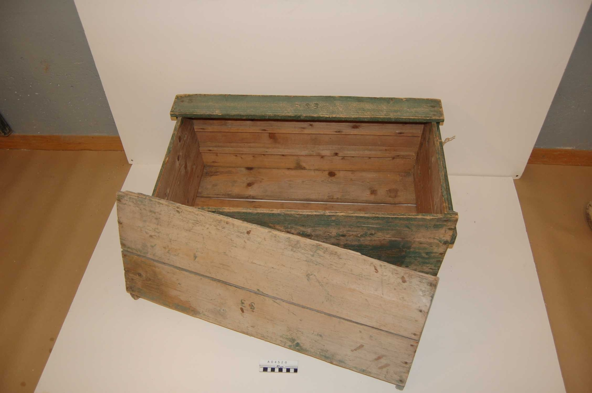 Grønn, malingslitt kasse (A.04520 a).  Løst lokk (A.04520 b) som dekker nesten hele oversiden.  Full-lengde trelister som bærehåndtak på kortsidene. Runde luftehull i sidene. Langsgående lister innvendig som støtter til løse bunner for  tre lag med bærkurver.
