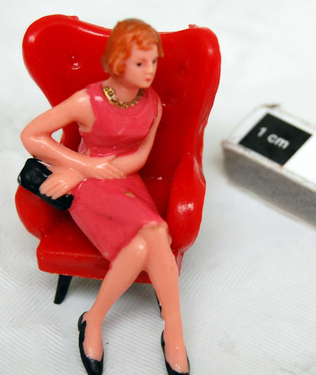 Sett med sofa og 2 lenstoler, sittende  kvinne og mann. Stolene i rødt med svart understell. Figurene er malt. Kvinnen har knekort kjole uten ermer, og håndveske. Mannen langbukser skjorte og vest.