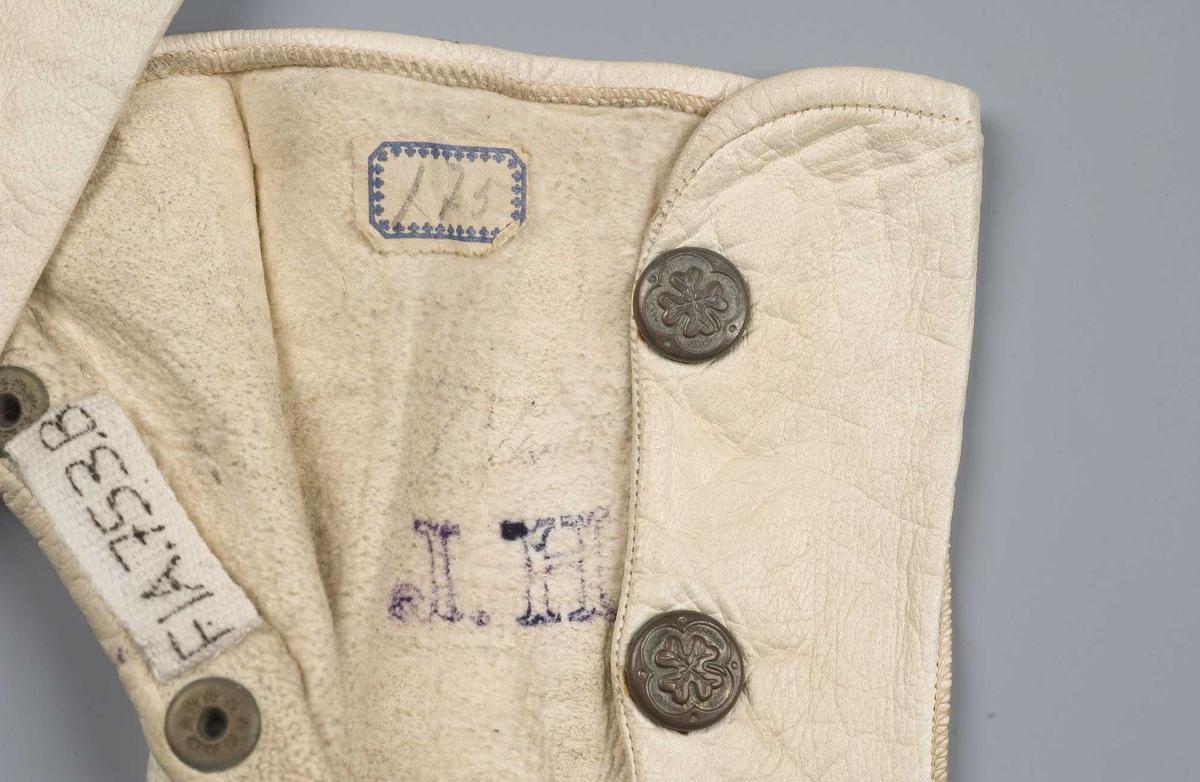 Hvite skinnhansker med to trykknapper som lukking ved håndleddet. Firkløvermønster på trykknappene. Uforet. I høyre hansker merket 7 1/4, papirlapp påført 175, initialer trykket J.H.