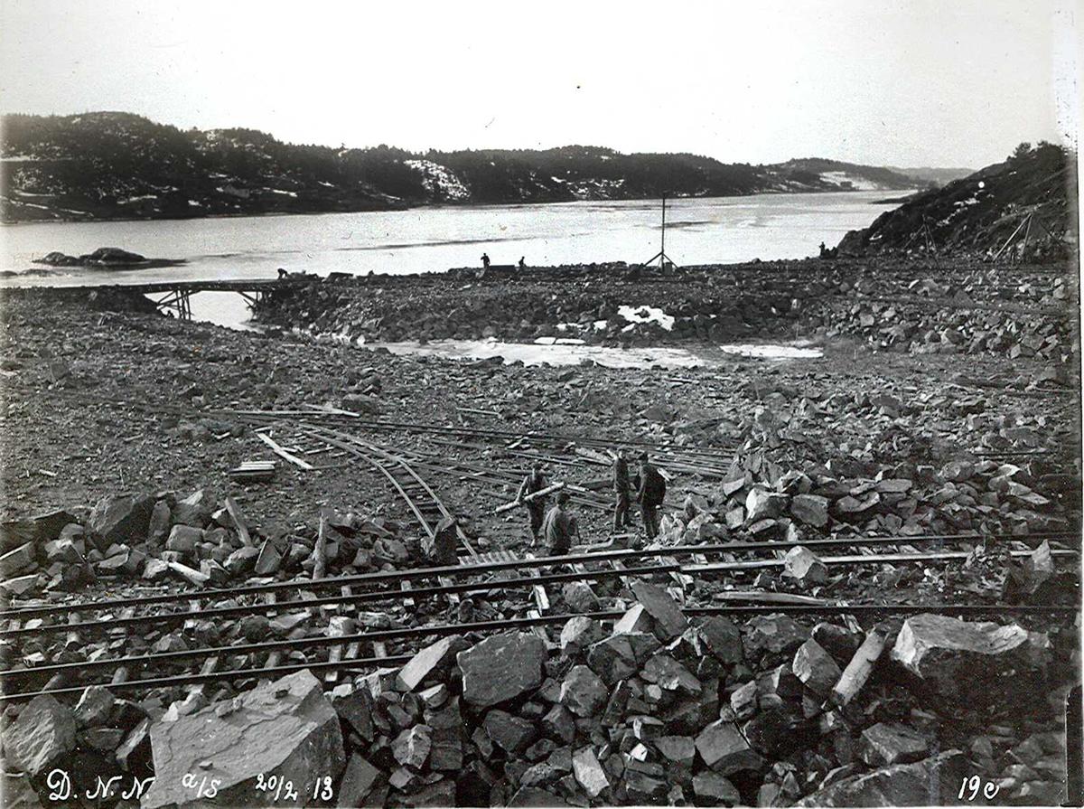 """""""20/02-1913"""" Nitriden. Utsprengning og planering av fabrikktomten. Utfylling mot Tromøysund. Tromøy i bakgrunnen. Til høyre skal bygning for materiallager, verksteder og kontorer bygges."""