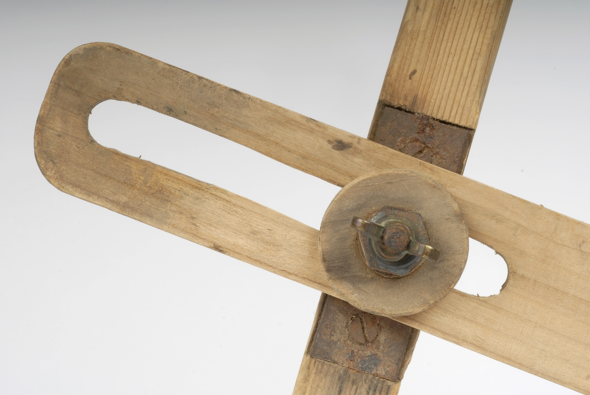 Bena av nåletre, tverrtre av lauvtre. Tverrtreet festet til ene benet med to skruer, en skrue med strammer kan beveges i spalte i tverrtreet for å regulere passeråpningen. Nederst har beina jernpigg og holk av kobber Snekkerredskap - reg.
