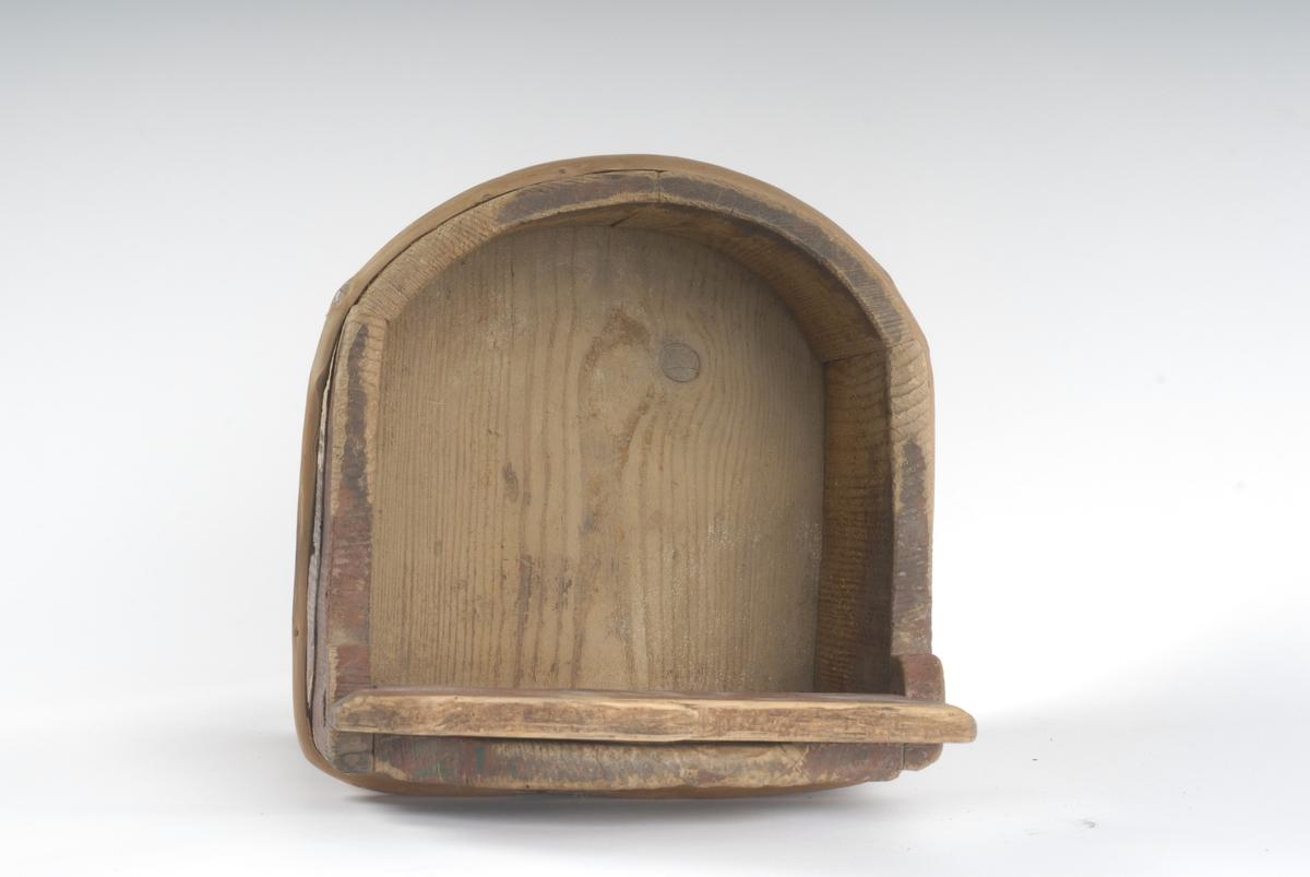"""Bakstykke av et stykke, forlenget, med hol for å bære eller henge opp. Ellers fire staver, tilnærmet halvsirkelformet botn. Har hatt minst to gjorder, bare en bevart. Et bevegelig lokk er tappet inn i sideveggene innved bakstykket. Tidl.reg.: """"Saltkar, Johs. Fløtten""""."""