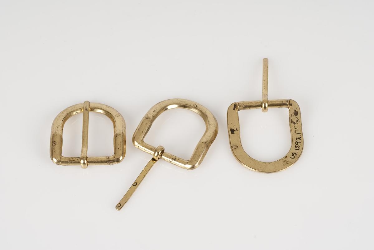 Beltespenne (A-G) av metall og i gullfarge. Beltespennene er bundet sammen med snor.