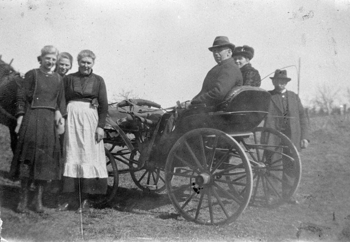 En gruppe mennesker står ved siden av to personer i karjol.