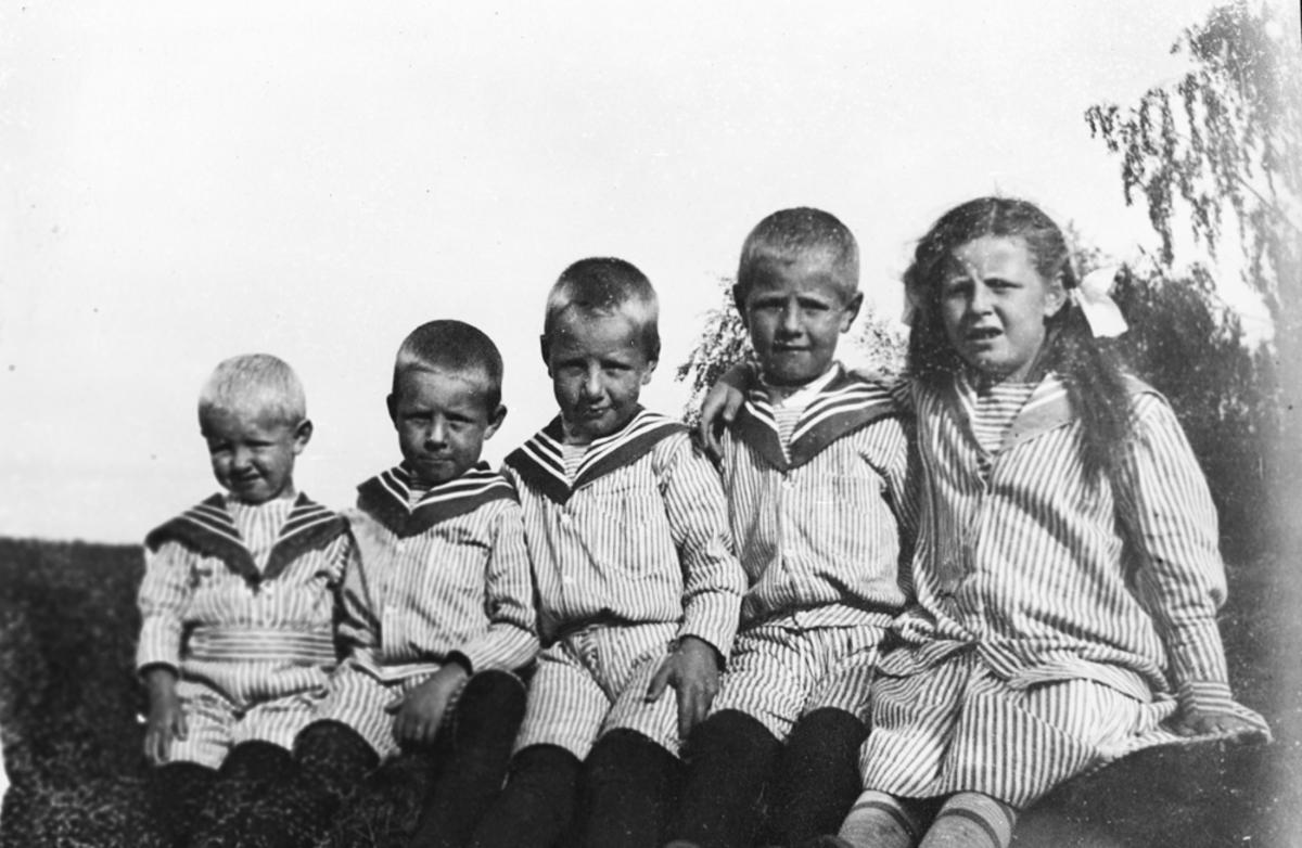 Fem barn på rekke i matrostøy.