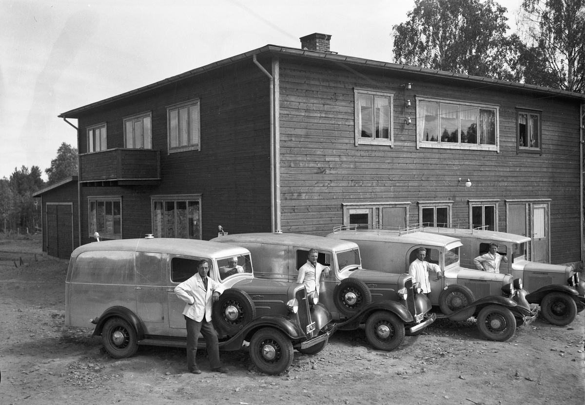 """Utenfor et bakeri. 4 Chevrolet kasse-/varebiler med kjennetegn C-14288, C-14092, C-14369 og A-18305. 13.05.2013: De to nærmeste Chevroletene er årsmodell 1936. I Norges Bilbok 1935 står C-14369 på en Chevrolet 1933 varebil tilh. Albert Haugan, Fjellstrand, Nesodden. Det kan stemme med bil nr. 3 fra v. Den har buet dørprofil karakteristisk for varebiler bygd av N. Jacobsens karosserifabrikk, men også benyttet av Automobilfabrikken og M. Urianstadstads karosserifabrikk, som nettopp holdt til på Fjellstrand. Kilde: Asbjørn Rolseth: Håndverk på hjul. Der er det på s. 595 foto av samme C-14369, men med annet farveskjema og påmalt tekst: """"Albert Haugan. Bakeri og konditori. Fjellstrand tlf 17"""". A-18305 var en Chevrolet 1931 varebil, tilh. Peder Olsen, Thv.Meyers gt. 47, Oslo iflg. Bilboken 1935. Bildet er trolig tatt da de to 1936-modellene (og funkishuset?) var nye, neppe på 50-tallet. Skrevet av: Ivar E. Stav"""