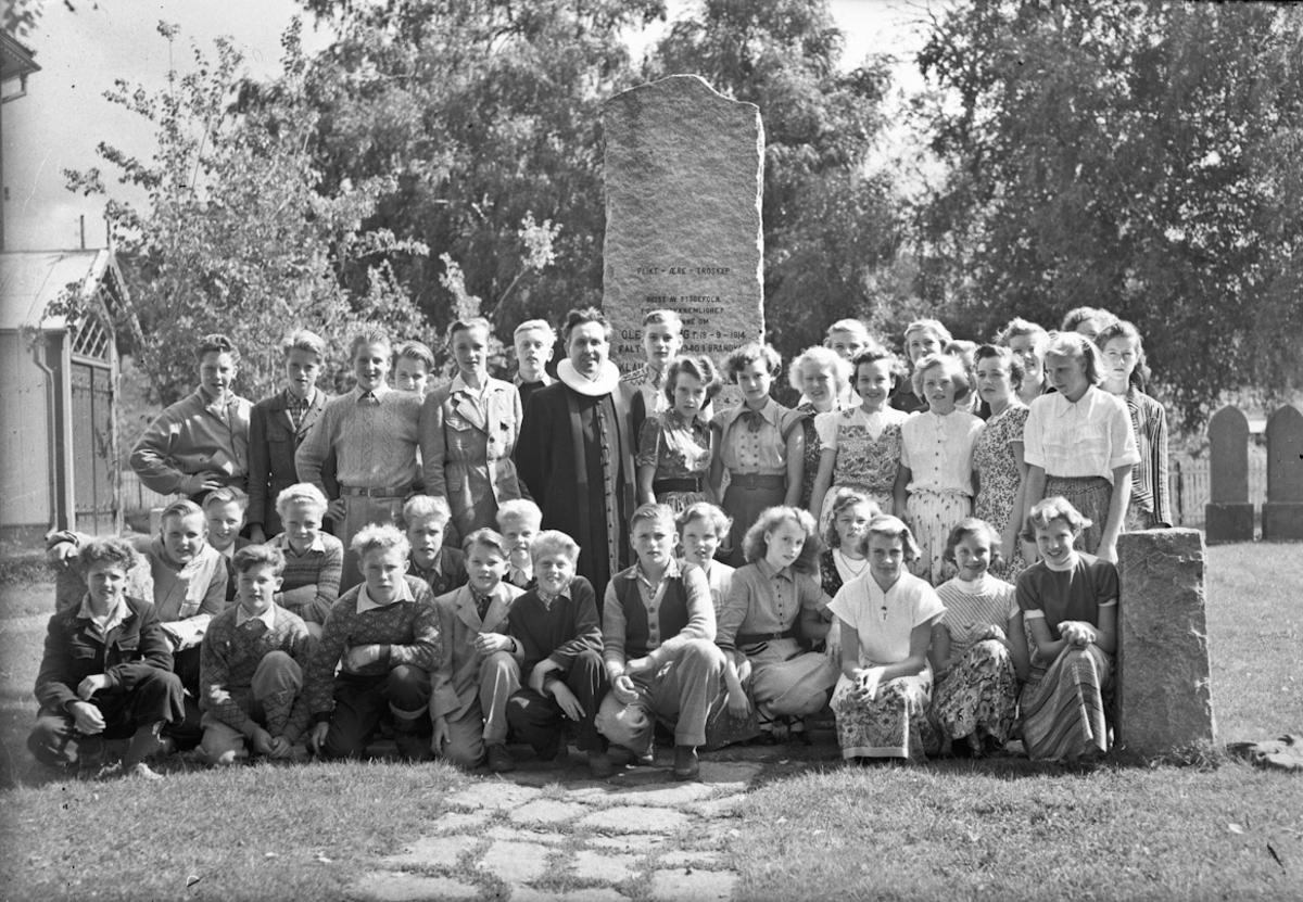 Konfirmanter foran minnesmerke over falne under krigen.