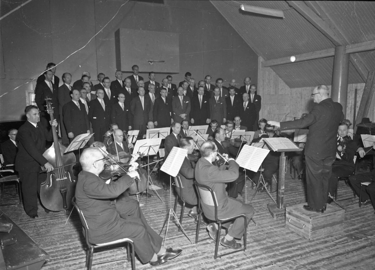 Eidsvoll mannskor(?) og et orkester. Alf Røvang, Odd Otterlei, Svein Underdal og Vidar Engen på bildet.