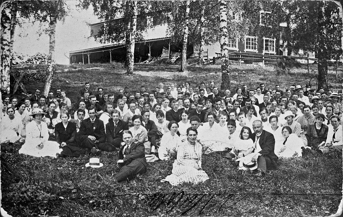 Elevstevne ved Eidsvoll Folkehøyskole. Jon. Sørensen foran til høyre med en av døtrene. Fruen sitter noe til venstre for dem. Bygningen i bakgrunnen er nordre del av uthuset.