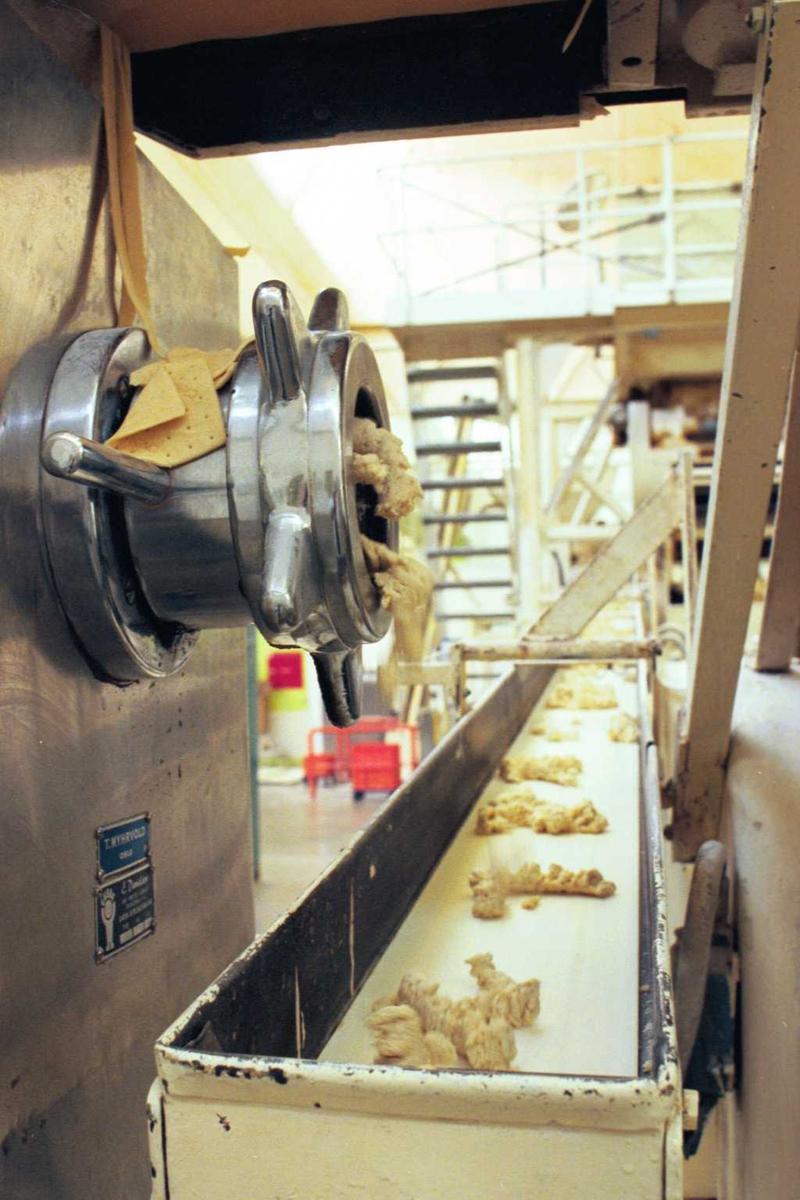 Deig fra utstikkingen føres tilbake til inntaket. Maskiner, deig, kjeks, Cream Cracker, fabrikkmiljø