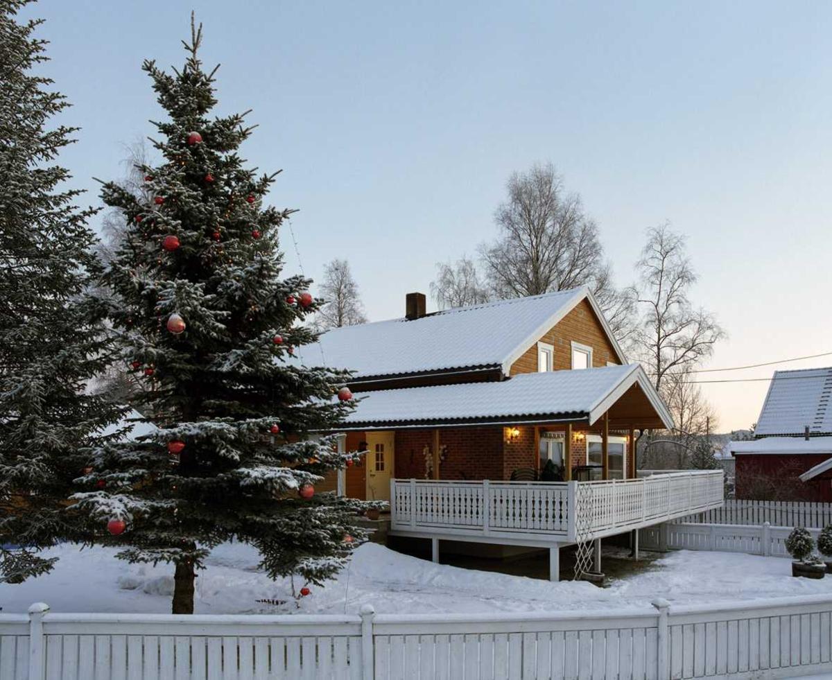 Julebelysning  Hvite lys og røde julekugler på gran ved enmannsbolig