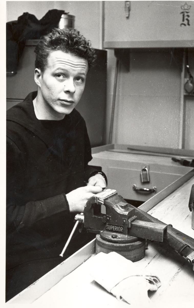 "Tjueen foto fra fregatten KNM ""Oslo"" under tjeneste vinteren 1967 i Nord-Norge. Livet om bord, fra artilleriverkstedet"