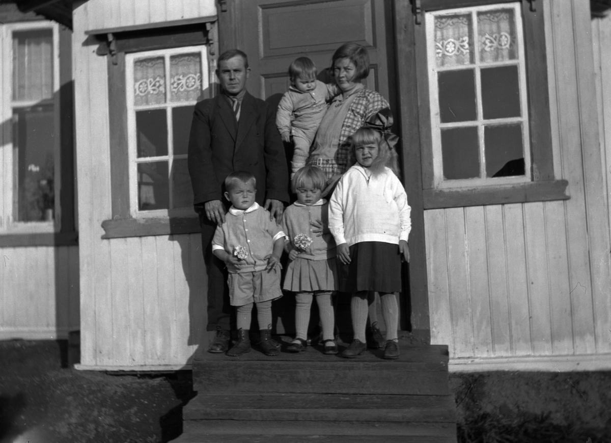 Familie på trappa ved inngangen til et hus.  Bildet er tatt på trappa i Vestby i Løten. Personene er Peder og Olea Talbak (Rasch) og barna deres. Den eldste jenta hette Hjørdis. Barnet på armen hette Gunnar Jostein. Begge disse barna døde så tidlig, som ca. bare 10 og 2 år gamle. Tvillingene foran er Sverre Talbak og Oddveig Holmen.
