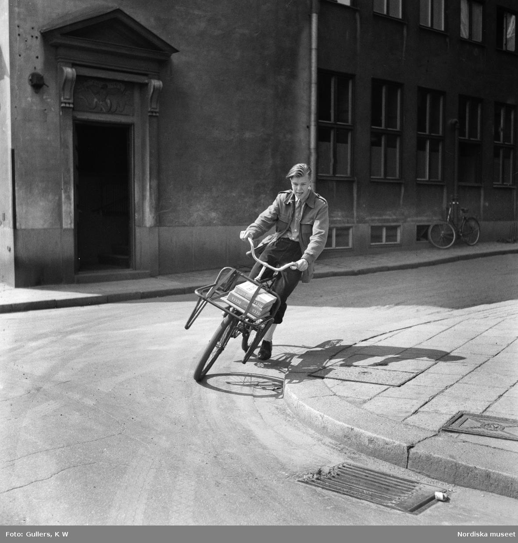 """Cykelbud i Stockholm. Bertil Parmryd 14 år svänger ut från Bredgränd i Gamla stan,  mot Skeppsbron i dåtidens vänstertrafik. På pakethållaren ligger paket med texten """"Aktas""""."""